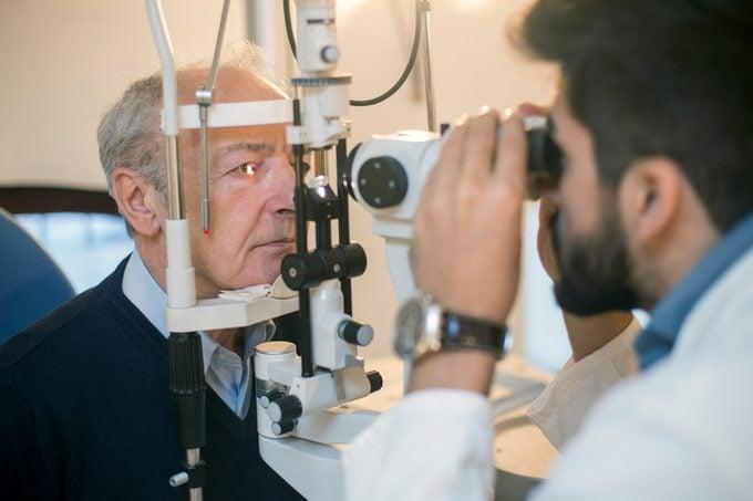 senior man having eyes examined by optometrist