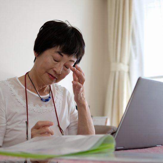 Senior woman rubbing eye while working at home